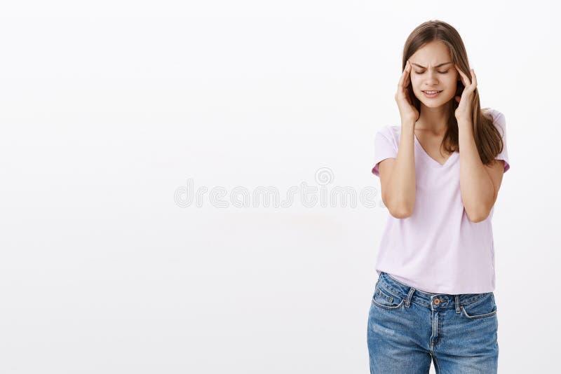 Положите ваш разум совместно Портрет интенсивной милой европейской девушки с глазами каштановых волос закрывая держа руки на виск стоковые фотографии rf