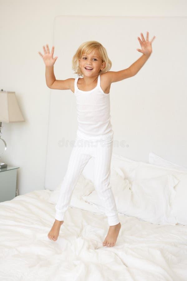 положите детенышей в постель девушки скача стоковое изображение