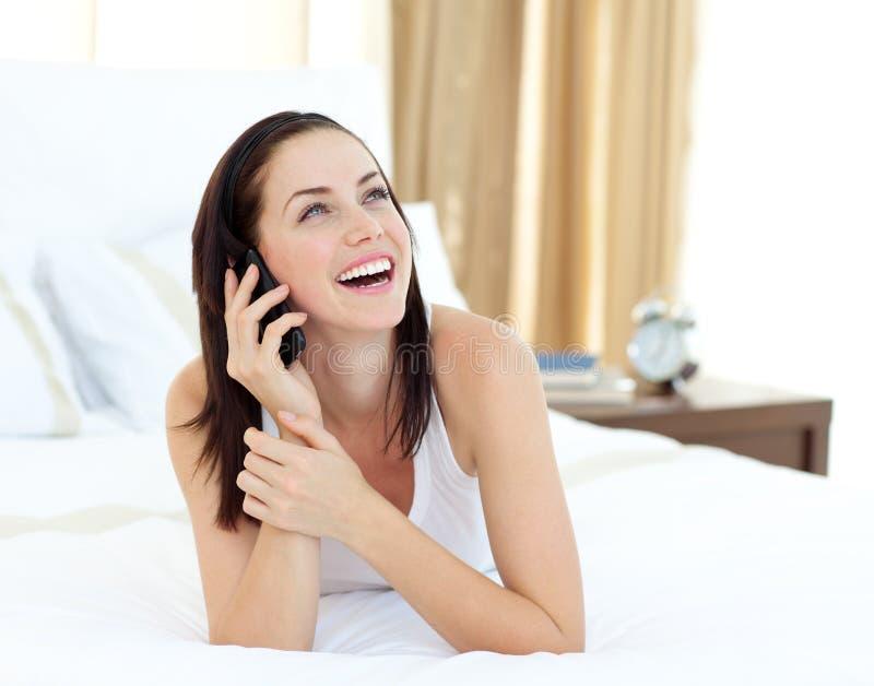 положите ее лежа женщину в постель радианта телефона стоковая фотография rf