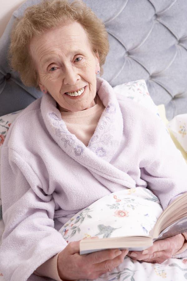 положите книгу в постель ослабляя старшую женщину стоковая фотография