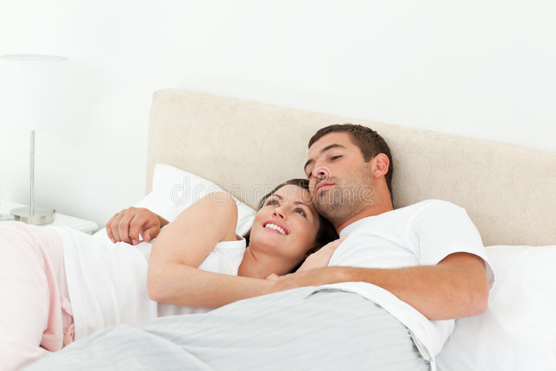 положите ослаблять в постель пар лежа задумчивый совместно стоковая фотография rf