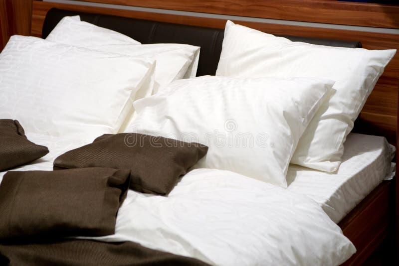 положите современные подушки в постель стоковое фото