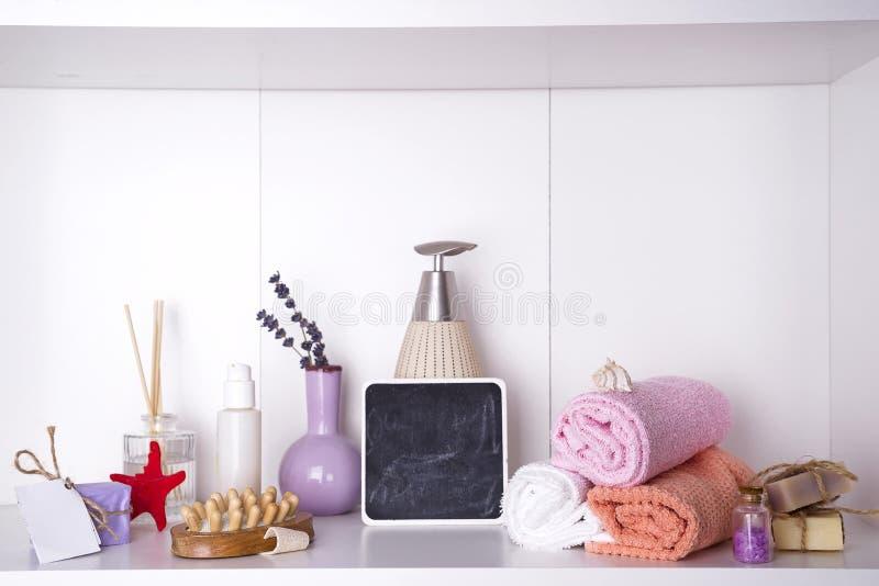 Полотенца в деревянном подносе с палочками ароматности, свечами, washcloths массажа и бутылкой с распределителем стоковое изображение rf