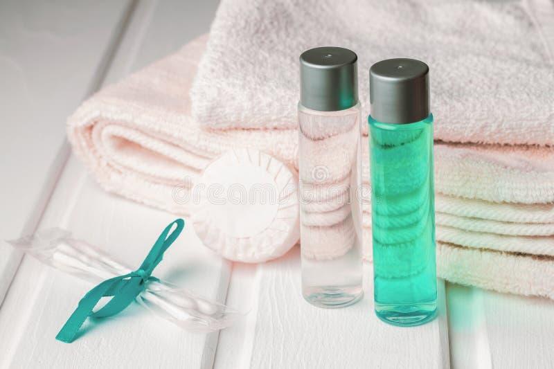 Полотенца и шампунь с гелем и мылом ливня с бутонами хлопка на таблице стоковые фото