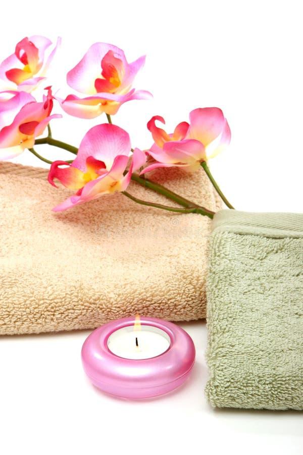 полотенца спы пинка орхидеи свечки стоковое фото
