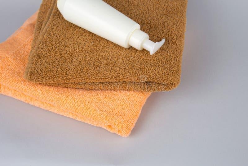 Полотенце Брауна и гель ливня на серой предпосылке сливк и полотенце стороны на таблице SPA косметик клеймя план Сложенная сливк стоковые изображения
