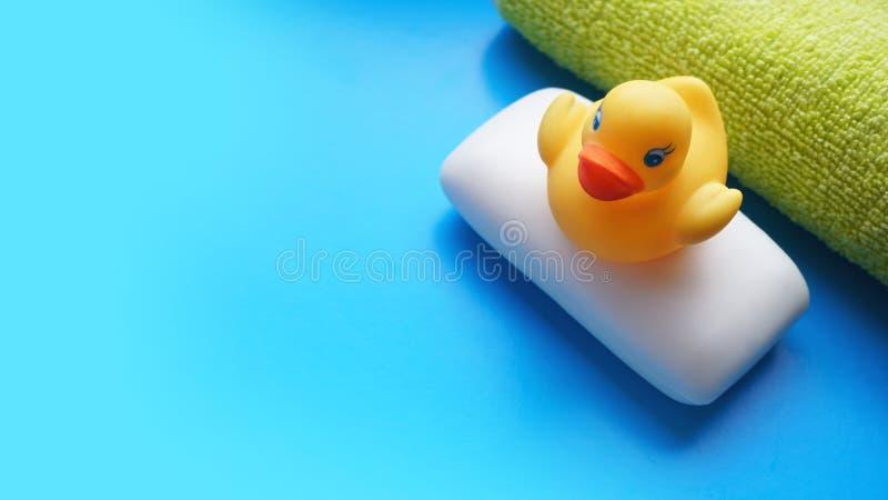 Полотенце, мыло и желтая утка игрушки на голубой предпосылке Плоское фото положения, взгляд сверху стоковая фотография rf