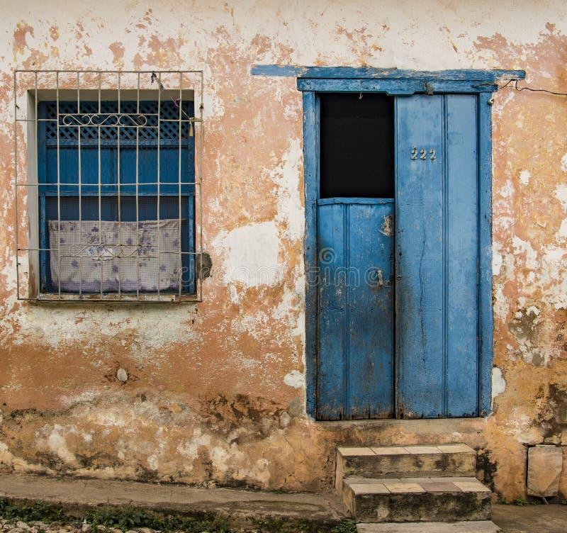Полуоткрытая синяя дверь плюс окно с решеткой на избитой желтой стене Ñ стоковая фотография rf