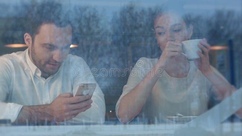 Получать женщины пробурил в кафе пока ее парень занятый с телефоном стоковое фото