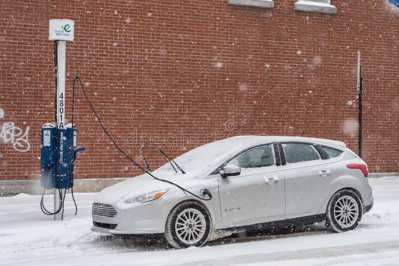 Получать электрического автомобиля поручил в Монреале во время пурги стоковое изображение rf