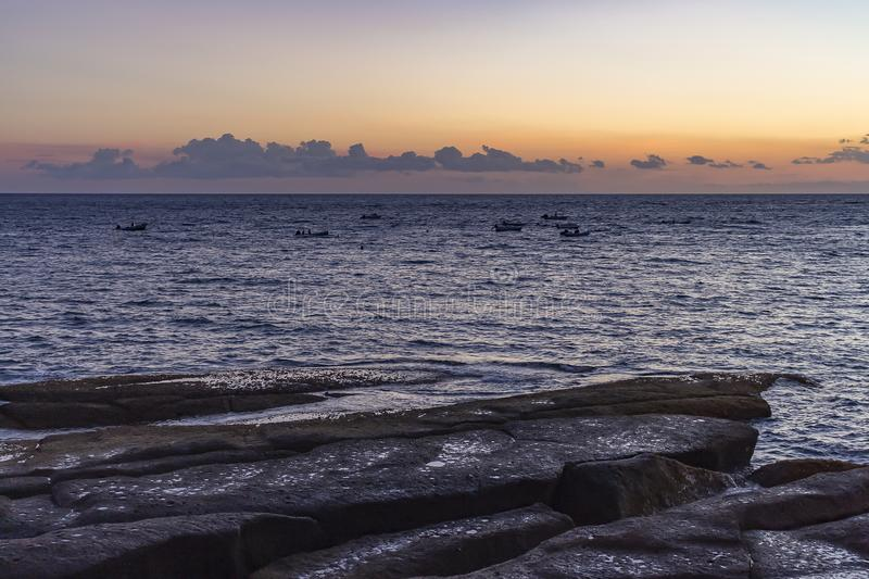 Получившиеся отказ рыбацкие лодки перемещаясь в море во время захода солнца вдоль скалистого побережья Ла Caleta, Косты Adeje на  стоковое изображение