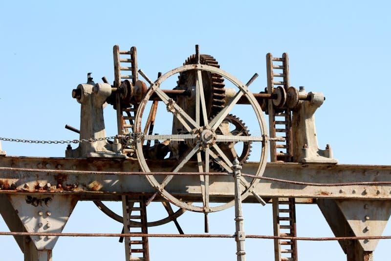 Получившийся отказ cogwheel запруды заржавел шестернями, который заперли с небольшой цепью для предотвращения несанкционированног стоковые фото