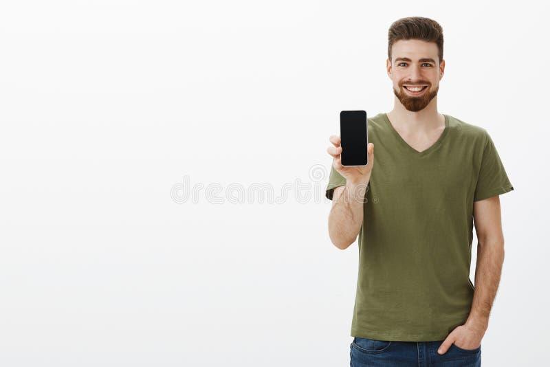 Получите внушительное устройство теперь Довольный уверенный симпатичный харизматический бородатый мужчина в экране показа футболк стоковое фото