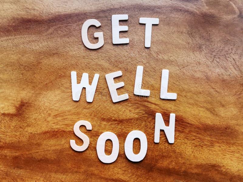 Получите хорошо скоро сообщение на деревянном столе стоковые фотографии rf