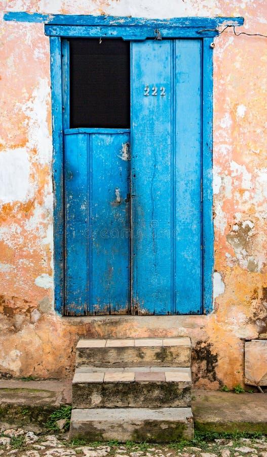 Полу-открытая голубая дверь на растрепанной желтой стене с каменными шагами стоковые фотографии rf