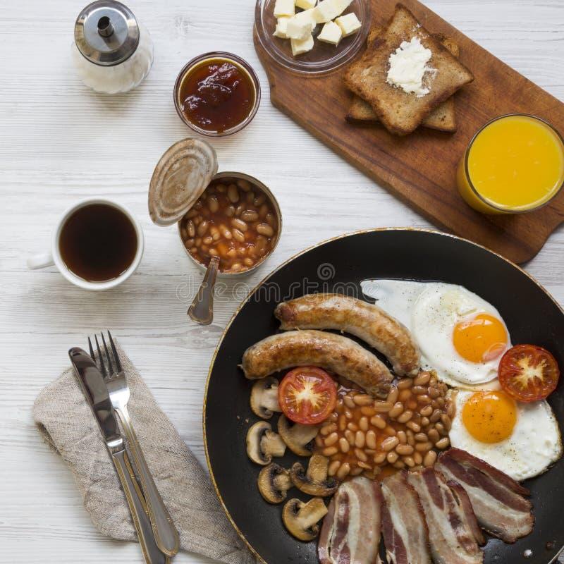 Польностью английский завтрак в лотке с яичницами, беконом, фасолями, сосисками и здравицами на белом деревянном столе, надземным стоковые изображения rf