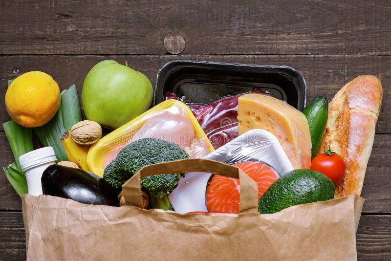 Польностью бумажная сумка различной здоровой еды на белой деревянной предпосылке плодоовощи, овощи, рыбы и мясо стоковое изображение