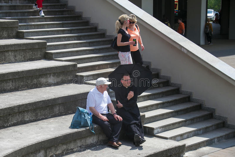 ПОЛЬША, КРАКОВ - 28-ОЕ МАЯ 2016: Говорить к паломникам и священникам на шагах базилики божественной пощады стоковое фото