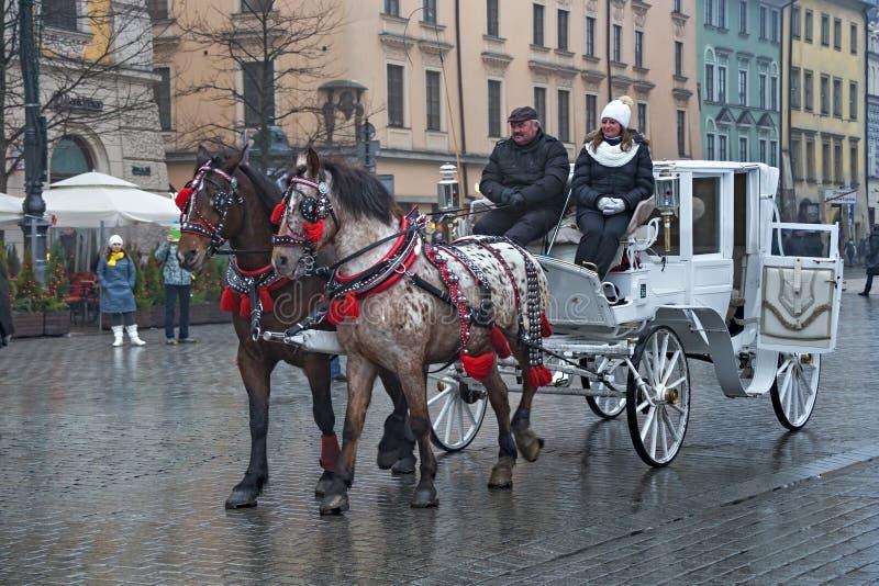ПОЛЬША, КРАКОВ - 1-ОЕ ЯНВАРЯ 2015: Экипажи лошади в oldtown в первом дне Нового Года 2015 стоковое изображение