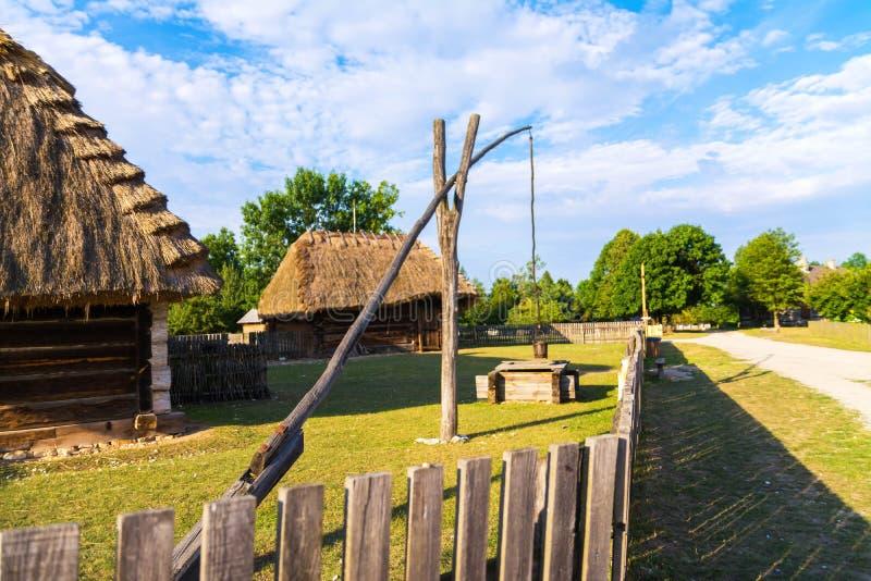 Польша, Kielce старые польские дома и shadoof на поле, колодец притяжки стоковое фото rf