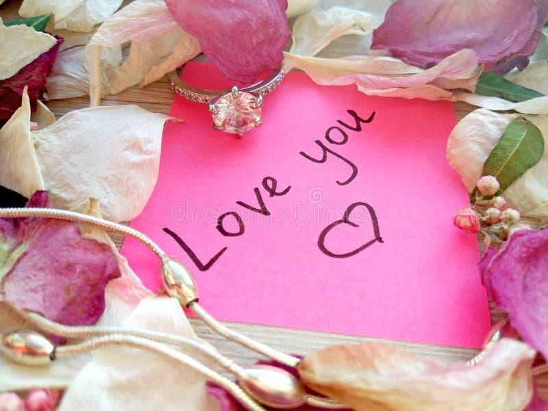Полюбите вас сообщение на розовом липком примечании с сухими лепестками цветка розы и орхидеи и серебряными кольцом и цепью ювели стоковые изображения rf