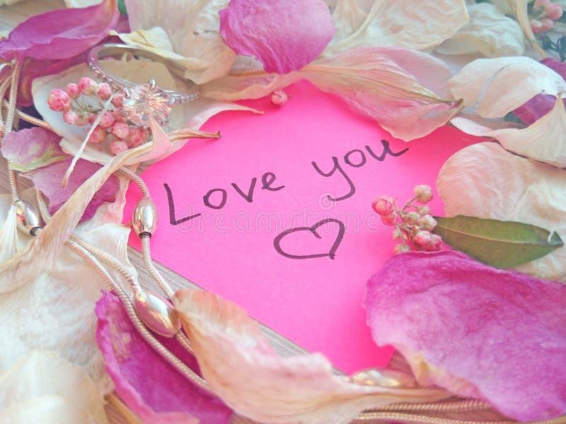 Полюбите вас сообщение на розовом липком примечании с сухими лепестками цветка розы и орхидеи и серебряными кольцом и цепью ювели стоковая фотография rf