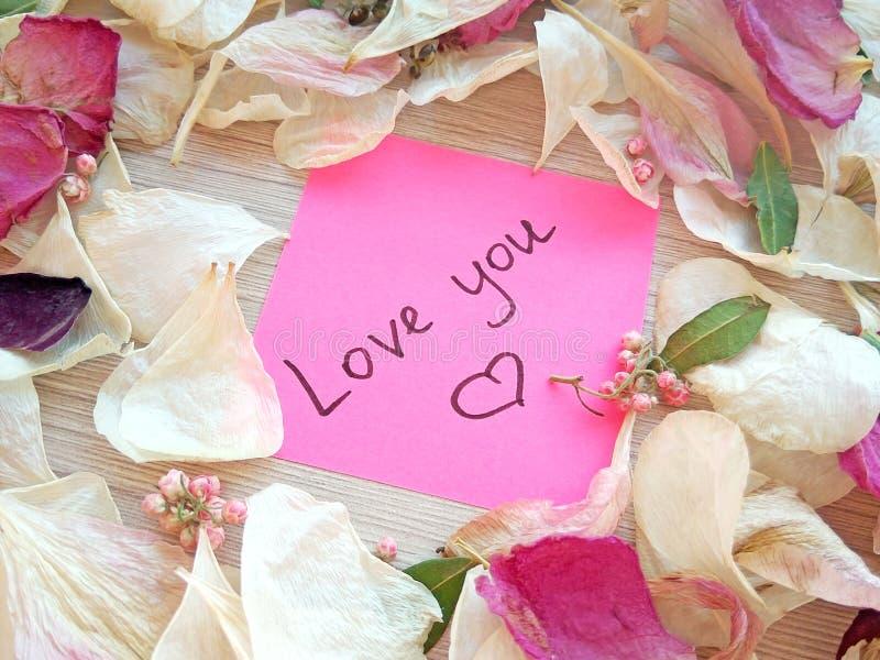 Полюбите вас сообщение на розовом липком примечании с сухими лепестками цветка розы и орхидеи на предпосылке деревянного стола стоковая фотография