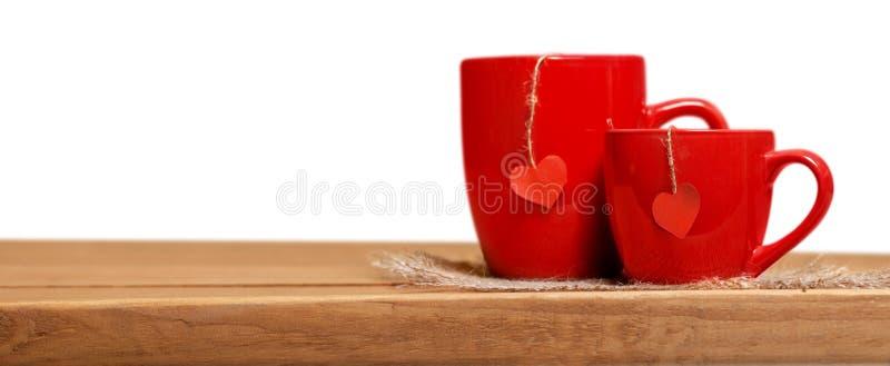 Полюбите, романские чашки концепции 2 красные с бумагой стоковая фотография