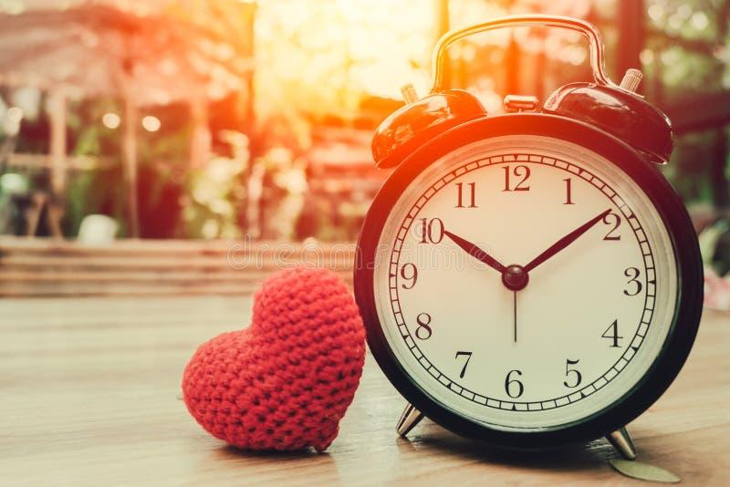Полюбите часы времен с красным символом сердца любить стоковое фото