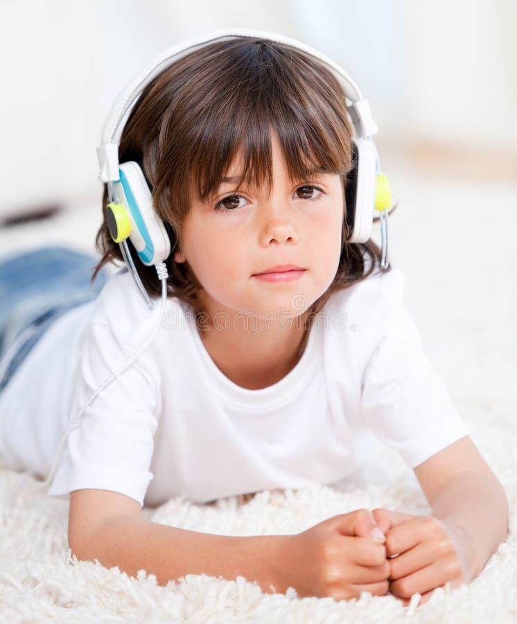 пол мальчика милый слушая меньшее лежа нот стоковое фото