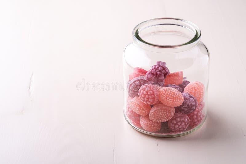 Помадки тросточек конфеты в форме сочных ягод в стеклянном опарнике на белой деревянной предпосылке стоковые изображения rf