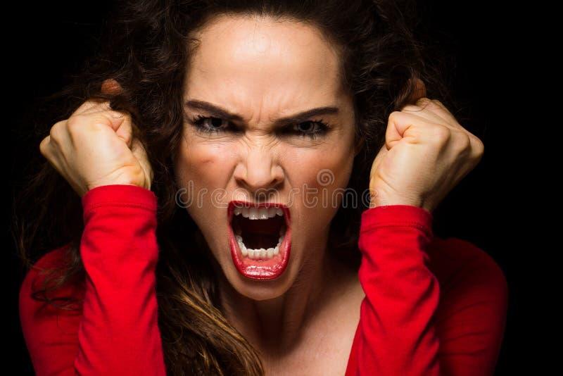 Поменяйте кулаки сердитой женщины обхватывая стоковое изображение rf