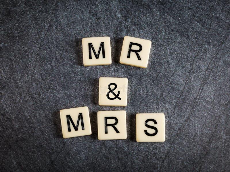 Пометьте буквами плитки на черных г-не & Госпоже правописания предпосылки шифера стоковые фотографии rf