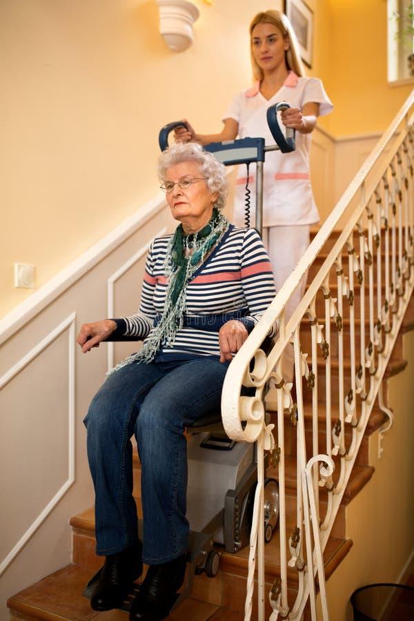 Помогает старшей старой неработающей женщине взобраться лестницы с machin стоковые фотографии rf