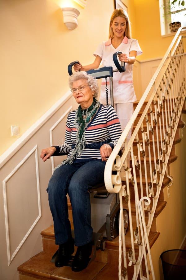 Помогает старшей старой неработающей женщине взобраться лестницы с машиной стоковые фото