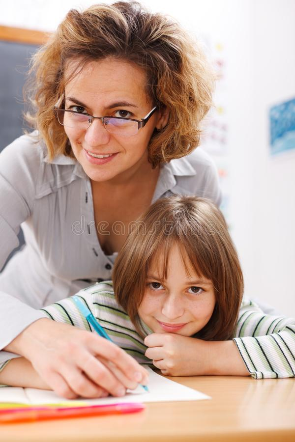 помогая сочинительство учителя школьницы стоковое изображение