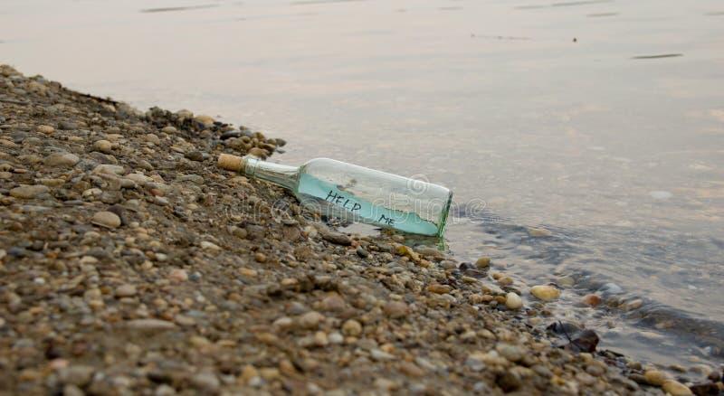Помогите мне сообщение в стеклянной бутылке стоковое фото rf