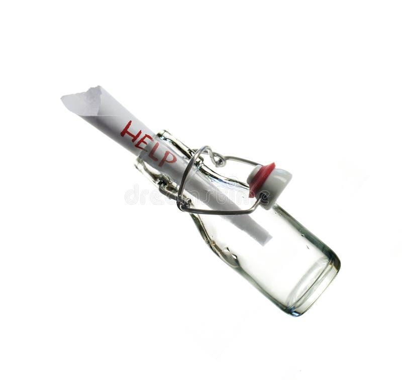 Помогите сообщению в стеклянной бутылке изолированной на белизне стоковая фотография rf