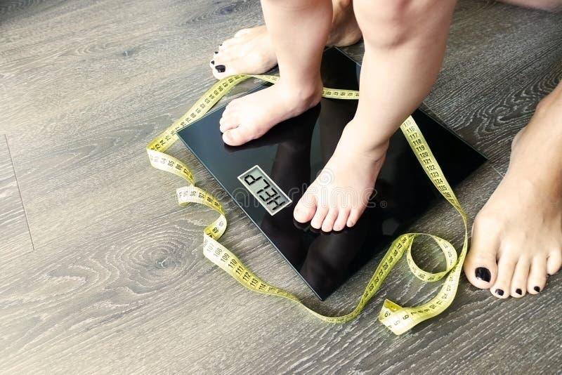 Помогите тучному или брюзгливому ребенку с малышом на масштабе веса, который наблюдал родитель стоковые изображения