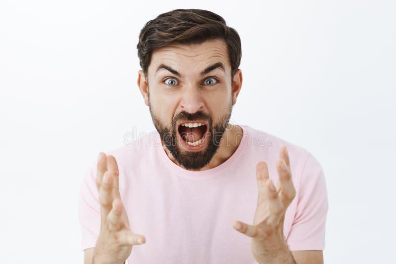 Помоченный парень выкрикивая от гнева и ненависти во время аргумента Портрет злодействованного надавленного кавказского мужчины с стоковая фотография