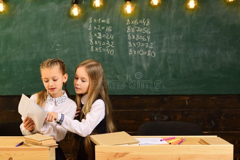 Помощь и намек 2 девушки намек и один другого помощи помощь и намек 2 девушек школы Пробовать помочь кто-то намек стоковое изображение