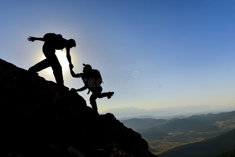 Помощь и поддержка на альпинистах саммита стоковые изображения rf