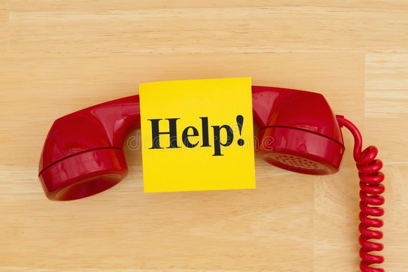 Помощь на липком примечании с ретро красным телефоном на текстурирова стоковое изображение