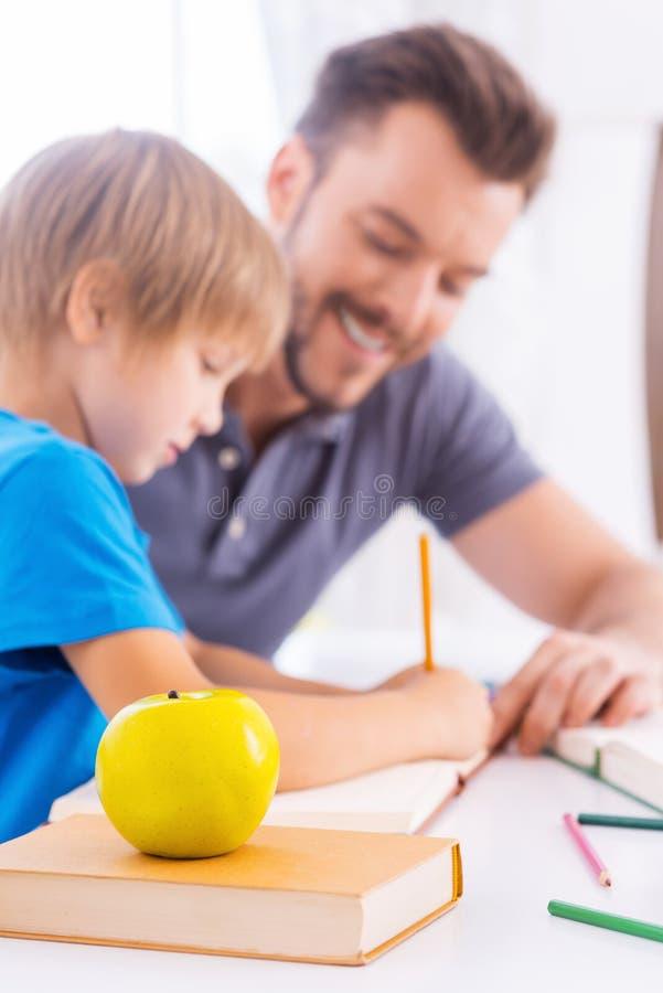 Помощь сына с schoolwork стоковая фотография