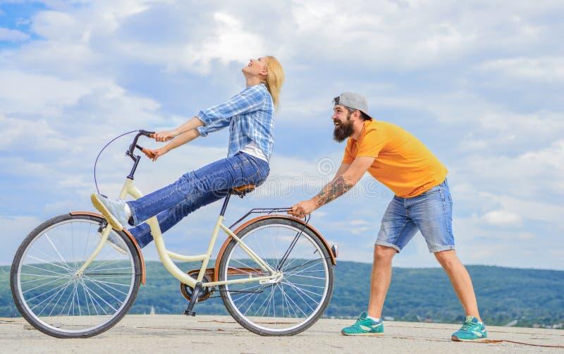 Помощь человека держит баланс и едет велосипед Как выучить ехать велосипед как взрослый Девушка задействуя пока парень поддержива стоковое фото