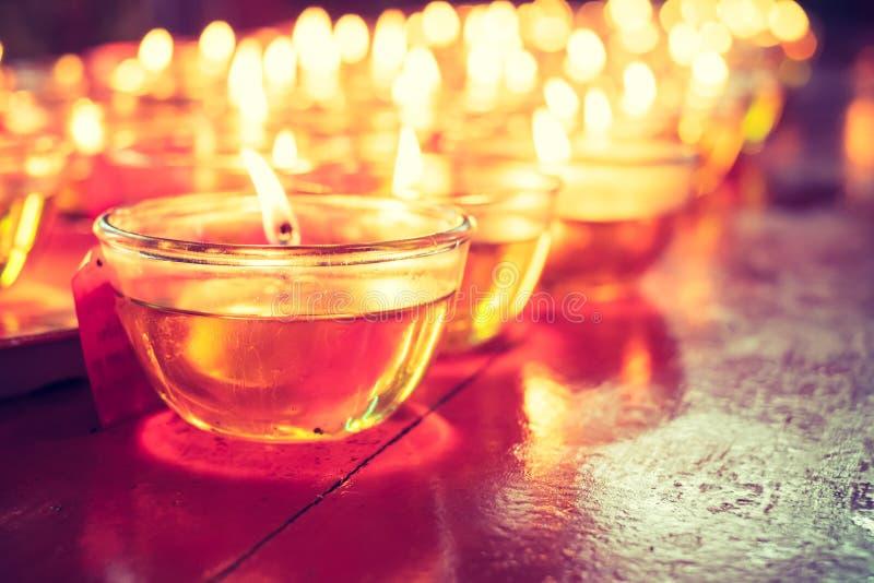 Помолите стекло свечи на деревянной таблице в китайском виске стоковое фото