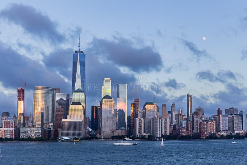 Понизьте горизонт и луну Манхаттана поднимая на голубой час стоковые изображения