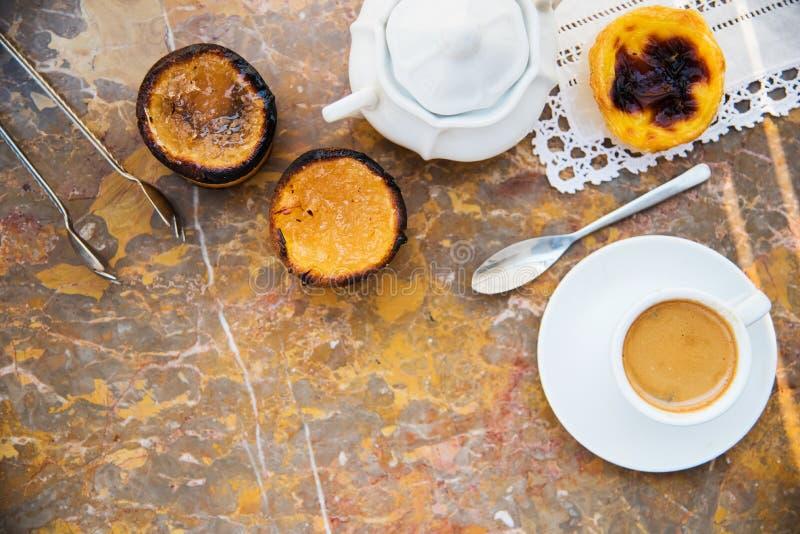 Понятый с кофе утра и тортами & x28; Pasteis de nata, типичное печенье от Portugal& x29; на естественной мраморной поверхности стоковая фотография