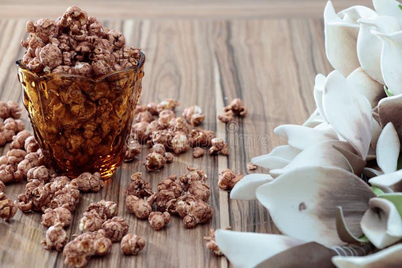Попкорн ароматности шоколада в желтом стекле и на коричневой деревянной таблице с предпосылкой белого цветка стоковое фото