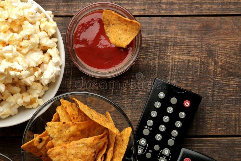 Попкорн и различные закуски, ТВ удаленное на коричневой деревянной предпосылке концепция смотреть фильмы дома над взглядом стоковое изображение